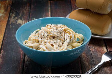 Fettuccine Alfredo classic Italian Pasta on a dark wood table.