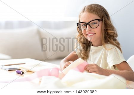 It is a pleasure. Contented little girl with glasses sewing and looking at the camera while sitting at the table