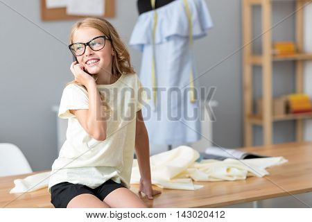 Like adult people do. Charming little girl talking on the phone and looking aside while sitting on the table with a mannequin on the background