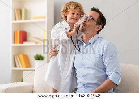It is very important. Charming little boy in a hospital gown examining a cheek of his father who making a grimace