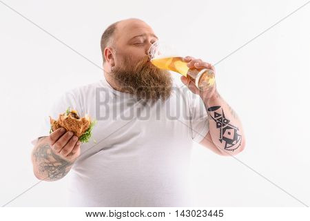 Fat man is enjoying cold beer. He is holding standing and holding sandwich. His eyes are closed with pleasure. Isolated