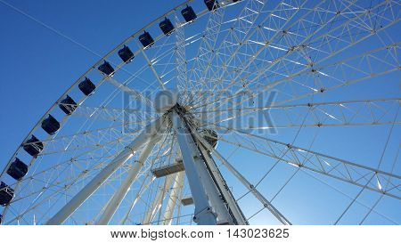 Ferris wheel in white and blue on a background of blue sky.