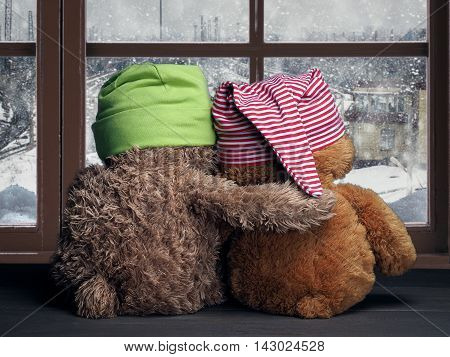 Two friends looking out the window at the falling snow and the city. Toys colorful hats bear cubs. Embrace the window. Concept - love friendship support