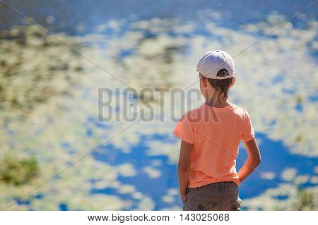 child standing by the pond and looking at the water. boy stands on the shore near the water. hands in his pockets. view from the back. blur, bokeh. empty space for your text