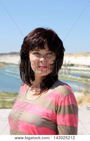 Cute young girl with slight smile looking away. Brunette on the background of the chalk quarry.