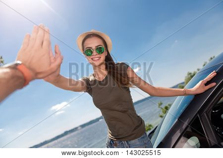 Nice to see you. Overjoyed smiling delighted woman standing near the car and giving high five while resting on the seaside
