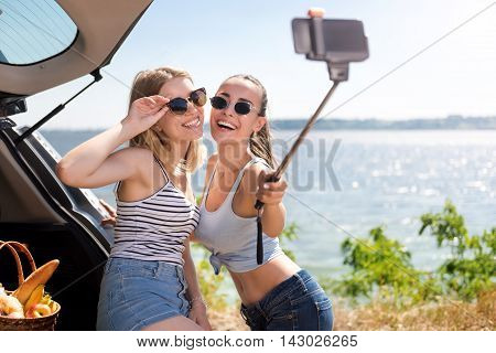 Life fully. Overjoyed young smiling friends making selfies and standing near car while resting near sea