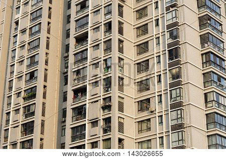 The many floors of a large skyrise apartment in Shanghai China in the late afternoon sun.