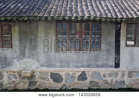 An old weathered building lining a water canal in Luzhi town in Jiangsu province china.