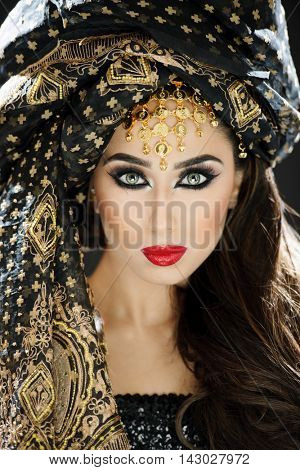 Portrait of a female model in exotic head turban and makeup and jewelery