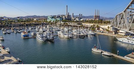 BARCELONA SPAIN - JULY 3 2016: The marina Port Forum in the north of Barcelona where lots of ships are moored. Nearby a electricity plant what guaranties the energy supply of the City