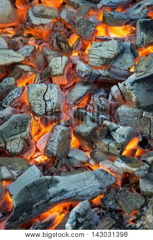Burning coal. Glowing embers smoldering in the fireplace. Stock photo.