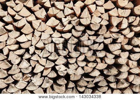 Neat stack of cut wood prepared for usage. Biomass fuel concept rural textured background.