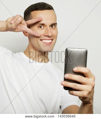 Cheerful young man in shirt holding mobile phone and making photo of himself