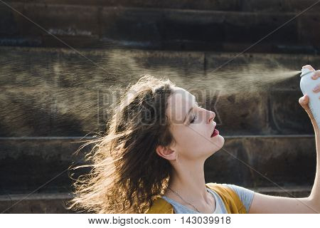 Photo of the Young woman refreshing face with thermal water. Enjoying, skin care, heat wave concept.