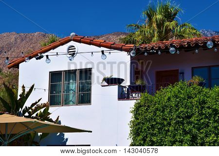 Spanish style hacienda villa surrounded by lush plants and Palm Trees with the San Jacinto Mountains beyond taken in Palm Springs, CA