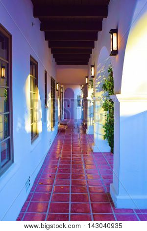 Outdoor hallway with Spanish tile and arches taken at a courtyard in a hacienda villa