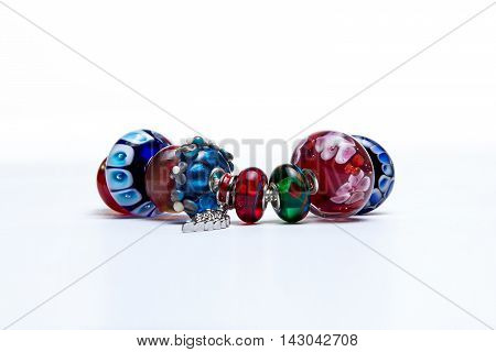 Bracelet with red and blue glass beads on white background