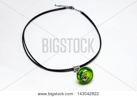 Accessory with green glass bead on white background