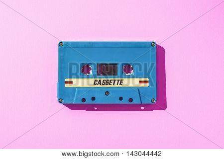 Old blue cassette tape on pink paper