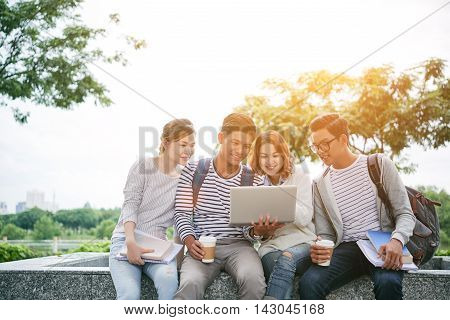 Group of Vietnamese students watching something on laptop on campus
