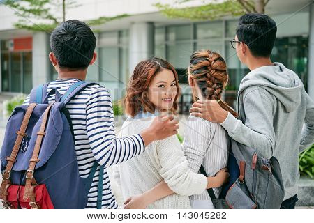 Female student hugging her classmates and looking at camera