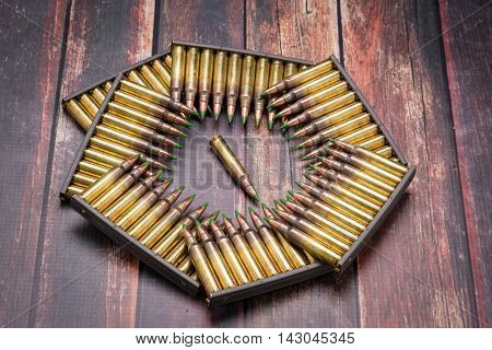 Ammunition .223/556 arrange in a pattern the shape of the Pentagon on dark wood surface.