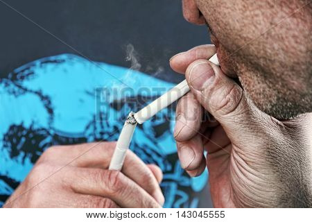 Men lighting a cigarette of his friend taken closeup.Toned image.