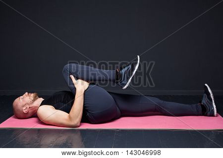 Young fitness man performing buttocks stretching on the mat