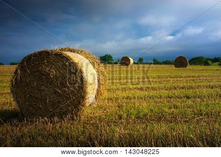 Haystack on a field of stubble. August countryside landscape. Masuria Poland.