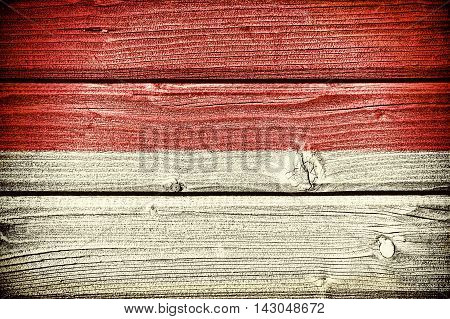 flag of Monaco painted on old grungy wooden background: 3d illustration