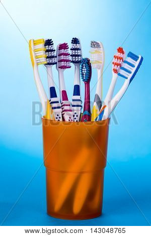 Various colorful toothbrushes in orange cup on blue background.