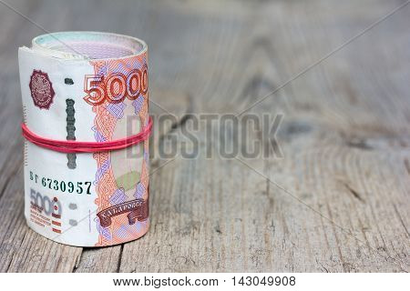 Roll Russian banknotes on old gray wooden board with cracks. Selective focus. with space for text placement