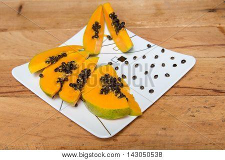 Ripe papaya sliced on white plate. Papaya