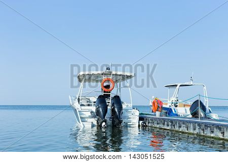 Two motor boats with big engines upraised moored at the pier in the sea