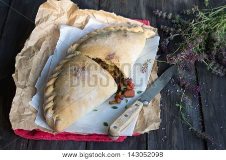 Italian pizza calzone with mushrooms, spinach and cheese on a wooden surface with a bunch of thyme, rustic style, selective focus