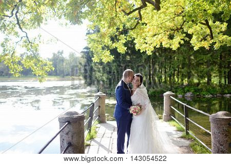 Wedding Couple On The Nature Is Hugging Each Other. Beautiful Model Girl In White Dress. Man In Suit
