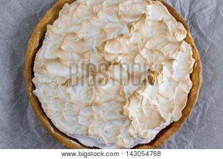 Top view on Sweet Meringue cake with strawberry jam on baking paper