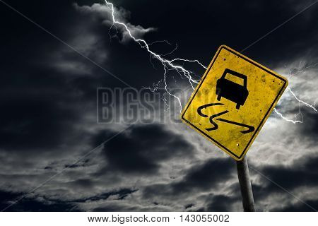 Slippery When Wet Road Sign With Stormy Background