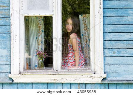 Sad little girl sitting on the sill and looking out the country house window. Outside view