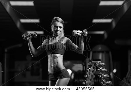 Black and white photo. Fitness woman pumping up muscles with dumbbells. Fitness woman in the gym. Perfect physique athletic young woman with six pack, perfect abs, shoulders and biceps.