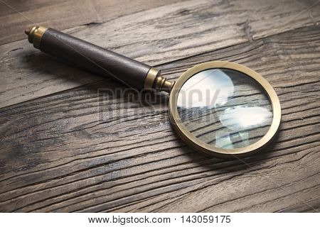 Retro style magnifying glass on a wooden tabe