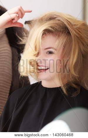 Hairstylist Combing Female Client Blond Girl In Hairdressing Salon