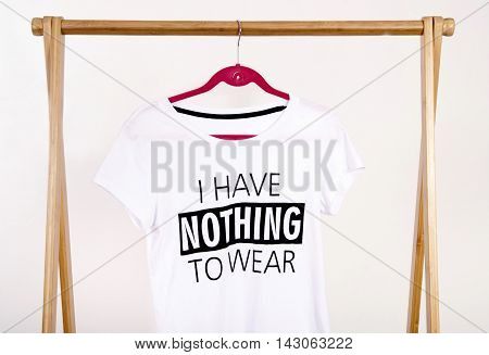 Wardrobe with an empty rack with noting to wear t-shirt.  Empty dressing closet with one t-shirt.