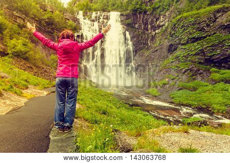 Travel freedom. Happy free tourist woman with arms raised outstretched up looking at Skjervsfossen waterfall between Voss and Granvin Hordaland County in Norway