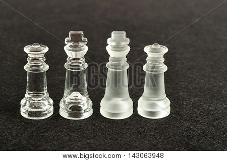Both the king and queen pieces that is used in a chess game displayed on a black background