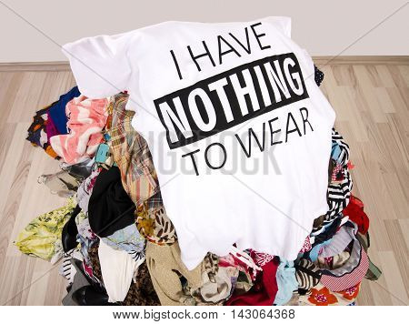 Big pile of clothes thrown on the ground with a t-shirt saying nothing to wear.  Close up on a untidy cluttered wardrobe with colorful clothes and accessories many clothes and nothing to wear.