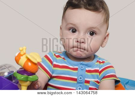 Cute baby boy sitting and playing with toys. Cute baby boy sitting and wondering.