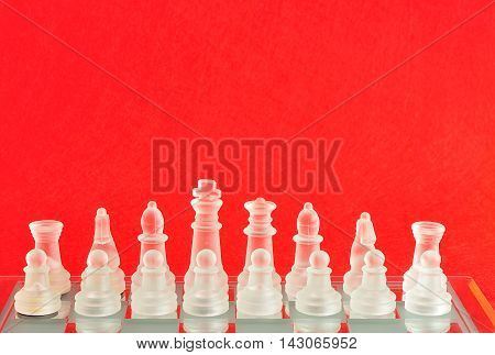 Chess pieces on a chess board isolated against a red background