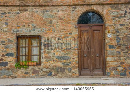 COLONIA DEL SACRAMENTO, URUGUAY - MAY 04, 2016: ancient house builded with bricks and stones, the door and the window are made of wood.
